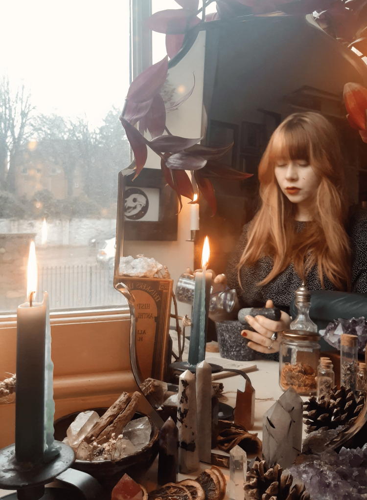 A photograph of Amy, the author. She has long ginger hair with a blonde streak. She is seen in the reflection of an antique mirror, mixing herbs in a black pestle and mortar. Crystal towers and lit candles can also be seen reflected in the mirror.